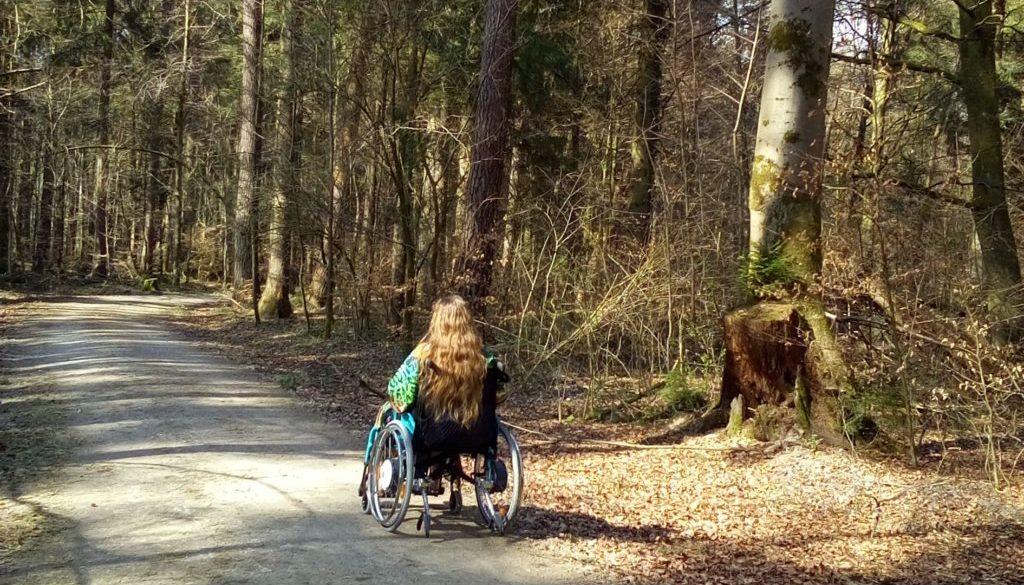 Patricia Koller im Rollstuhl auf einem sonnigen Waldweg