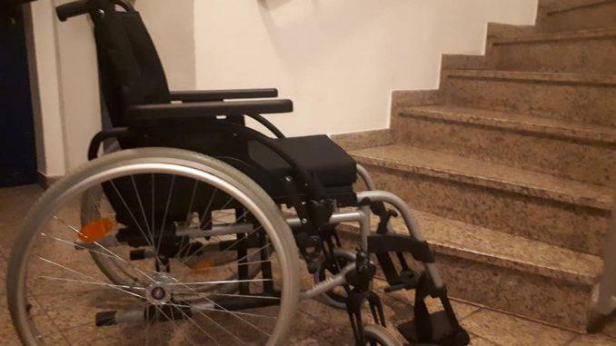Leerer Rollstuhl steht vor einer Treppe