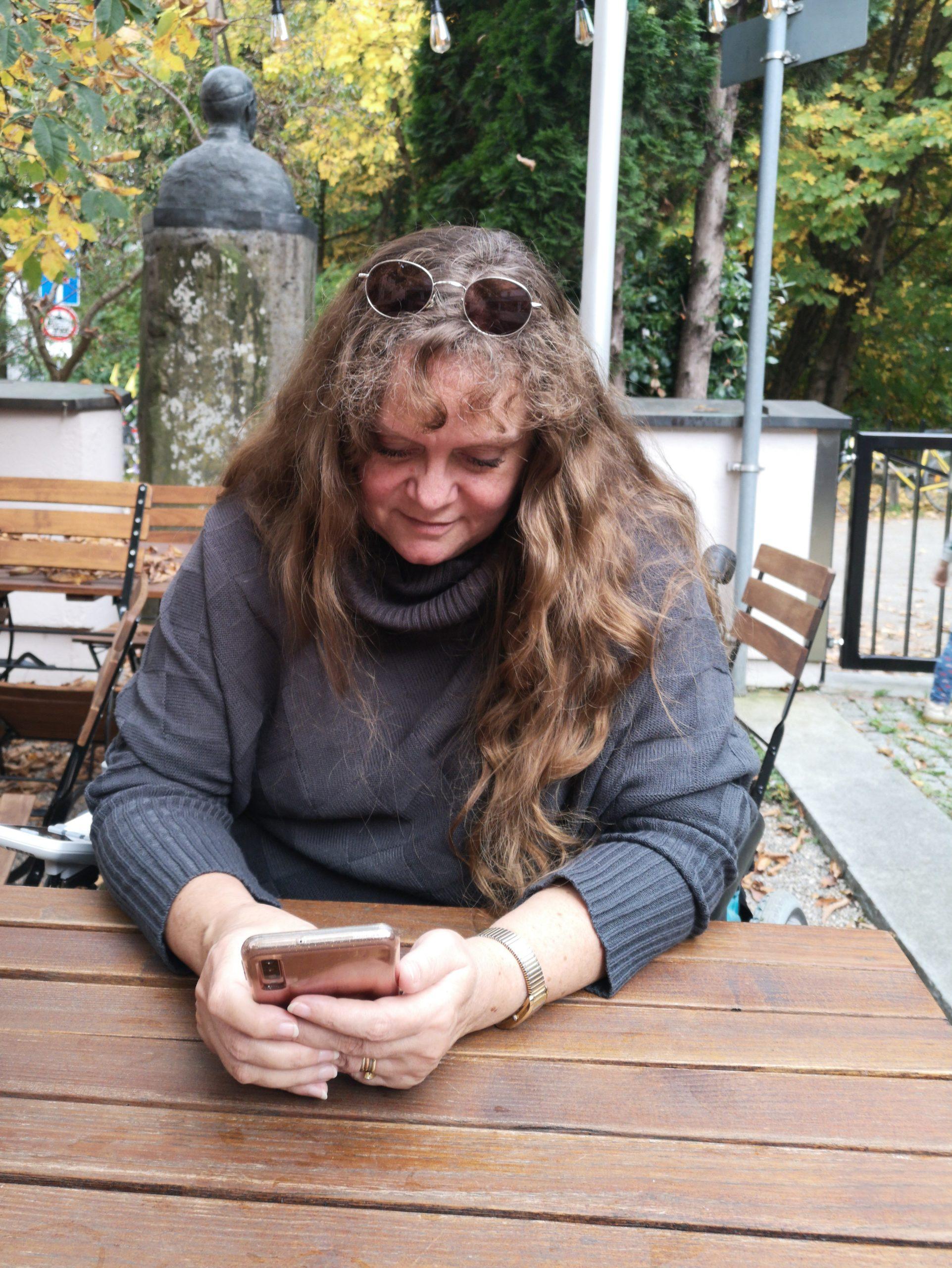 Patricia Koller im Biergarten bei dem Blick auf ihr Smartphone