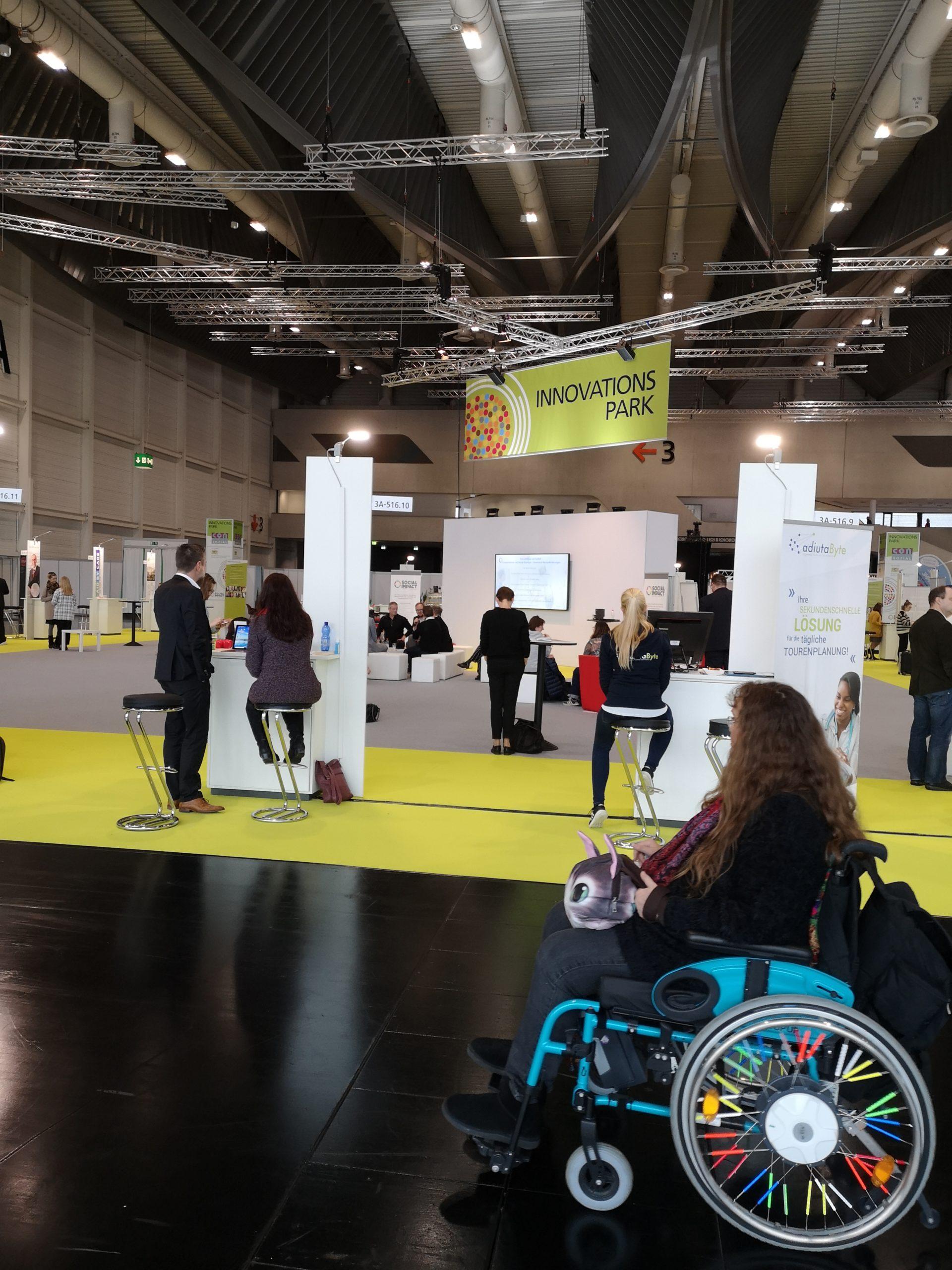 """Patricia Koller im Rollstuhl auf der ConSozial-Messe vor einem Schild mit der Aufschrift """"Innovationspark"""""""