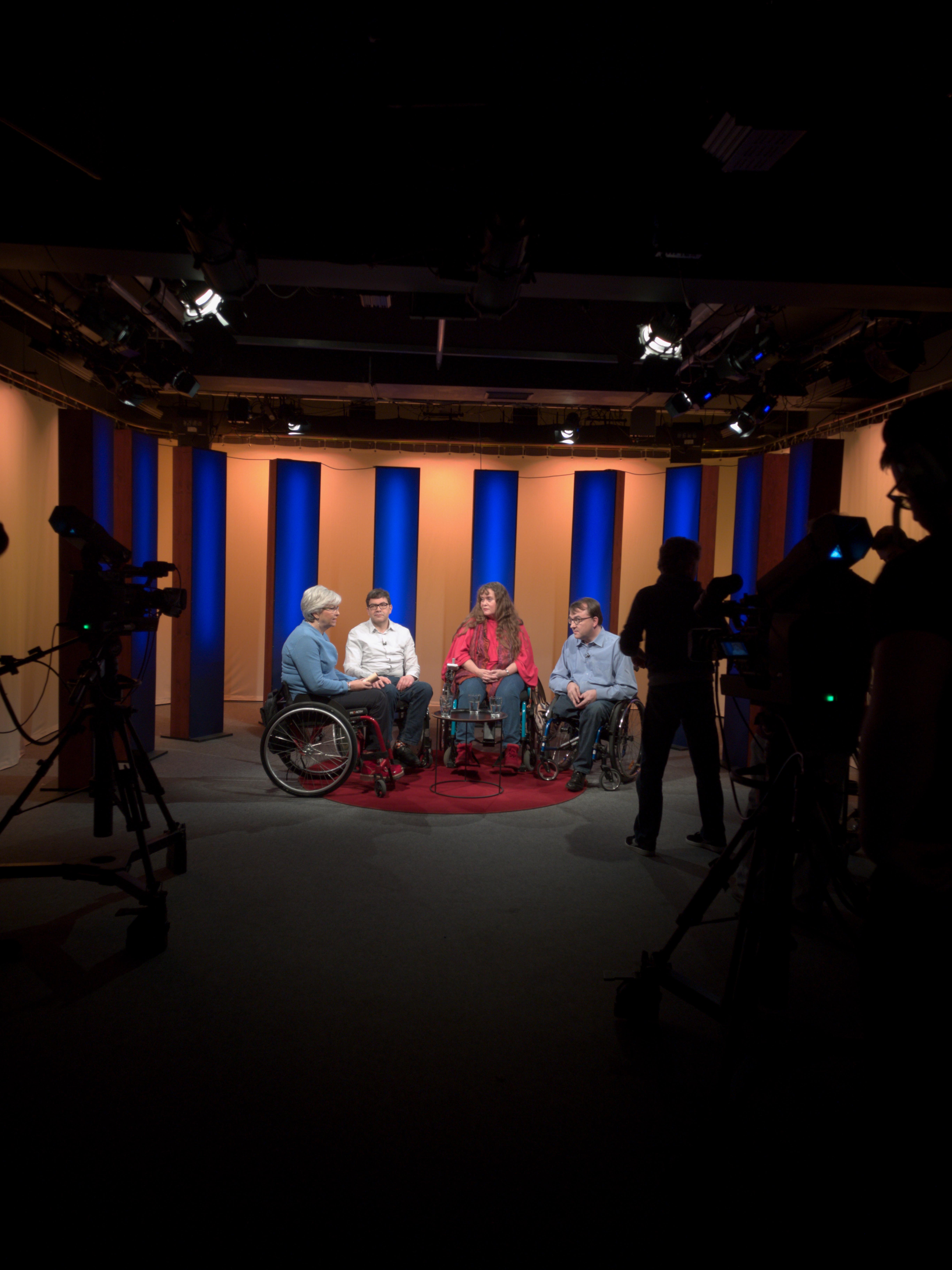 Fernsehstudio mit Kameraleuten im Dunkeln und im Licht sitzen die Moderatorin Anita Read und drei Stadtratskandidaten: Maximilian Dorner (Grüne), Patricia Koller (parteilos, Liste die LINKE) und Martin Blasi (Freie Wähler)
