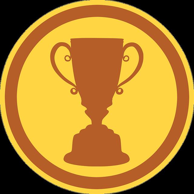 Ein goldener Pokal auf einem runden, gelben Untergrund.