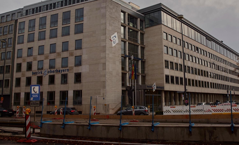 """Das Bild zeigt das Gebäude der Behörde """"Bezirk Oberbayern"""". Im Vordergrund ein SOS-Schild."""