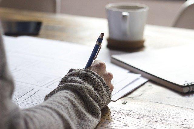 Ein Schreibtisch, auf dem der Arm einer Frau aufgelehnt ist. Sie hält einen Kugelschreiber in der Hand und macht sich bei einer Tasse Kaffee Notizen.