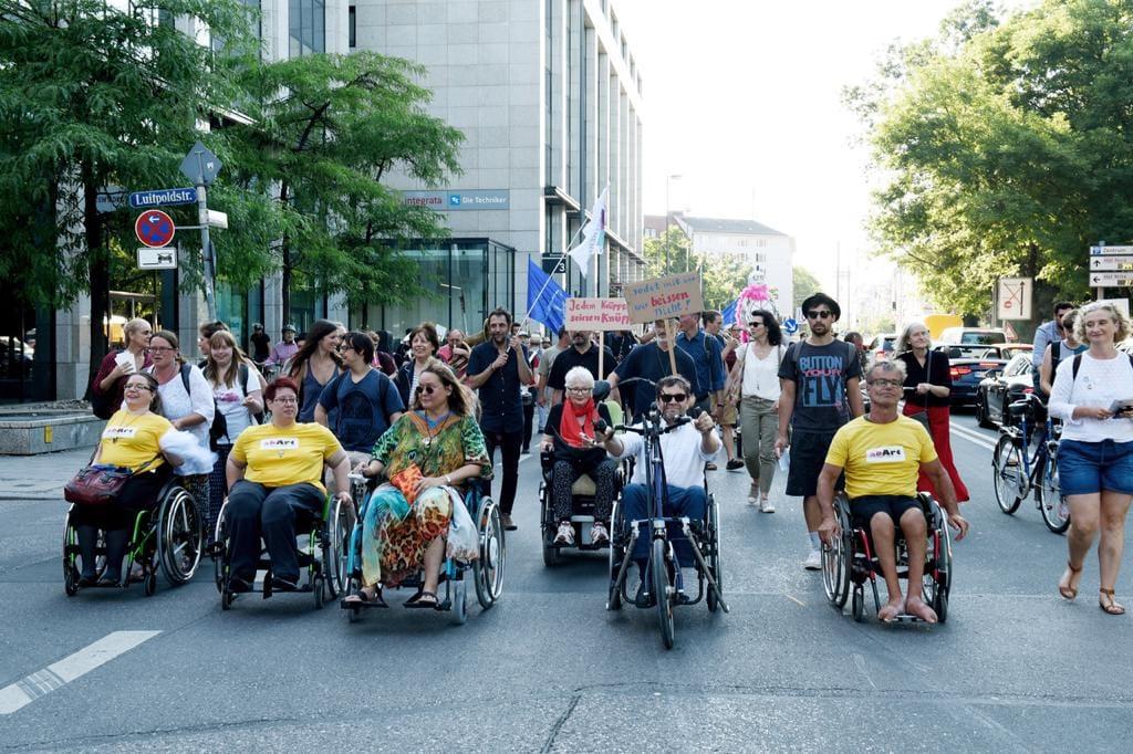 Mehrere Rollstuhlfahrer fahren bei der Köskivalparade nebeneinander mitten auf der Straße. In der Mitte Patricia Koller und Maximilian Dorner.