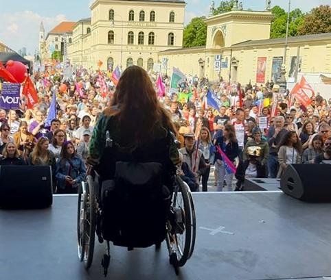 Patricia Koller im Rollstuhl auf der Rednerbühne vor einer sehr großen Menschenmenge
