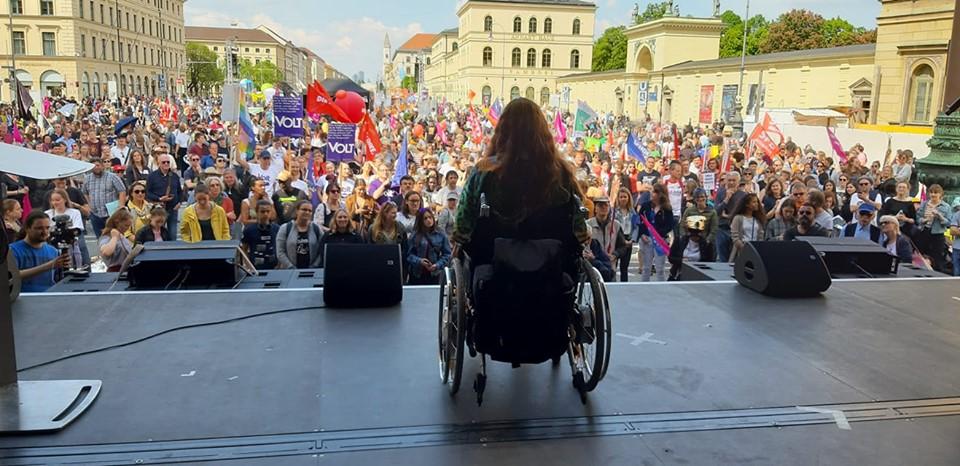 Patricia Koller bei der Ein-Europa-für-alle-Demo im Rollstuhl auf der Rednerbühne vor einer sehr großen Menschenmenge, die sich auf dem Odeonsplatz in München versammelt hat.