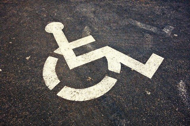 Ein sehr verschmutztes Rollstuhlfahrerzeichen auf einem Parkplatz.